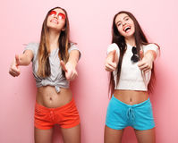 Positive friends portrait of two happy  girls - funny faces, emo. Tions, casual style, pastel colors. Smile and say ok Stock Image