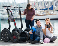 Positive friends posing near segways on shore Stock Images