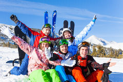 Positive friends with snowboards lifting hands up Royalty Free Stock Photography