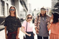 Positive friends walking around street Stock Images
