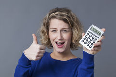 Positive and fun financial situation for young female student. Accountant and financial situation concept - positive female businesswoman with calculator in Royalty Free Stock Images