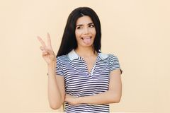 Positive funny female makes peace sign with hand, shows tongue, being in good mood, has long dark hair, has healthy skin, wears ca royalty free stock image