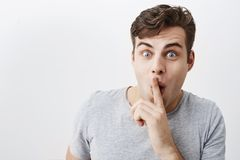 Positive funny man keeps fore finger on mouth, shows silence sign, with popped eyes, asks people to be quiet, making. Faces. Young male model says not to tell royalty free stock photo