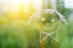 Positive funny smiley on rainy autumn window Royalty Free Stock Images