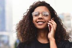Positive Gefühle Enthalten Sie Steigungs- und Ausschnittsmaske Abschluss oben des jungen Mischrassefrauengebrauches ein Telefon lizenzfreie stockbilder