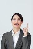 Positive Geschäftsfrau, die auf ein copyspace zeigt Stockfoto