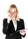 Positive Geschäftsfrau, die ein Klemmbrett anhält Lizenzfreie Stockfotografie