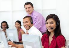 Positive Geschäftsleute mit Kopfhörer auf dem Arbeiten Lizenzfreie Stockfotos