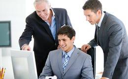Positive Geschäftsmänner, die an einem Computer arbeiten Lizenzfreie Stockbilder