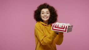 Positive girl afro hairstyle in hoodie opening gift box, unwrapping birthday surprise and expressing great happiness