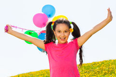 Positive girl with arms up and balloons in air