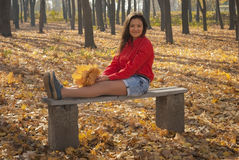 Positive girl in autumn park. Positive girl sitting on a bench in autumn park Stock Image