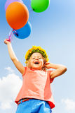 Positive girl with balloons wears flower circlet. In summer Stock Photo
