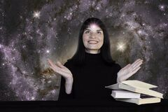 A positive girl in black clothes sits at a table with books against the background of the starry sky