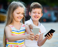 Positive girl and boy looking at mobile phones in park Stock Image