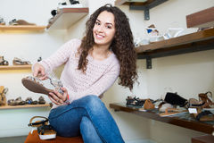 Positive  girl chooses summer shoes Stock Images