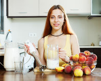 Positive girl cooking dairy beverages Royalty Free Stock Photo