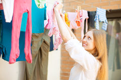 Positive girl drying clothes on clothesline Stock Photography