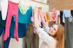Positive girl drying clothes Royalty Free Stock Photos