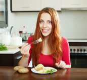 Positive girl eating jacket potatoes Stock Photography