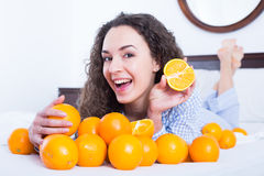 Positive girl eating oranges in bed Royalty Free Stock Photos