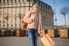 Positive girl is evincing gladness while walking with shopping bag. Full of joy. Cheerful young stylish woman in sunglasses is holding package and expressing royalty free stock images