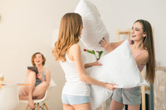 Positive girl fighting with pillows Stock Photography