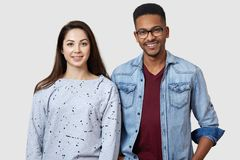 Positive girl and guy of different races poses against white studio wall, smile positively, express their happiness, dressed in royalty free stock photos