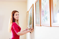 Positive  girl hanging  pictures Stock Photo