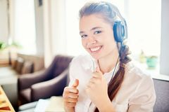 Songs for happiness. Positive girl in headphones looking at camera with toothy smile while enjoying songs from playlist stock photo