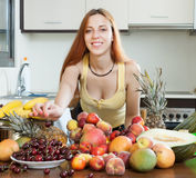 Positive girl with heap of fruits Royalty Free Stock Images