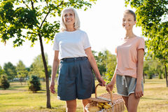 Positive girl and her grandmother carrying a picnic basket. Happy life. Cheerful senior women and her granddaughter carrying a picnic basket while resting in the Stock Images