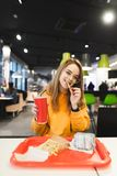 Positive girl holding a glass with a drink in hand, eating french fries, looks at the camera and smiling. Funny girl student eating fast food at the restaurant stock photo