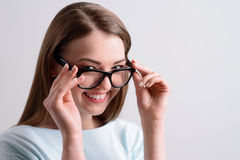 Positive girl holding her glasses. Optimistic view. Overjoyed delighted charming girl touching her glasses and expressing gladness while smiling on grey royalty free stock photography
