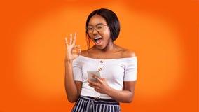 Free Positive Girl Holding Phone Gesturing Okay And Winking, Orange Background Royalty Free Stock Photography - 169064447