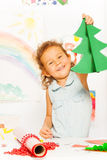 Positive girl holds carton Xmas tree standing Stock Photo