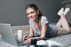 Positive girl with laptop surfing Internet. royalty free stock photo