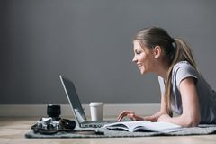Positive girl with laptop surfing Internet, laying on the floor. Planing trip stock photos