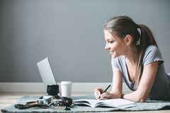 Positive girl with laptop surfing Internet, laying on the floor royalty free stock photos