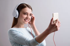 Positive girl listening to music. My hobby. Cheerful content beautiful smiling young woman holding smart phone and listening to music while expressing gladness royalty free stock photography