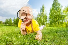Positive girl with magnifier lays alone on  grass Royalty Free Stock Photo