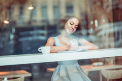 Positive girl making notes Stock Photography