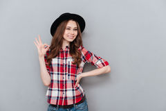 Positive girl in plaid shoort showing ok gesture and winking Stock Photography