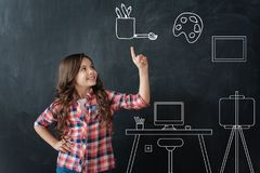 Positive girl pointing up while being the lesson of Art. Creative child. Cute happy emotional girl pointing her finger up and talking about famous picture stock images