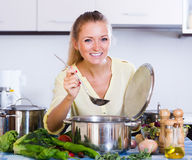 Positive girl preparing  veggie soup at home Stock Images