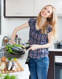 Positive girl with raw fish in frying pan Royalty Free Stock Photos