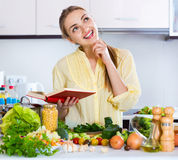 Positive girl reading book with recipes of vegetables Royalty Free Stock Photography