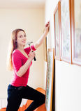 Positive  girl in red hanging  pictures Royalty Free Stock Image