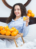 Positive girl with ripe oranges and glass of juice Stock Photography