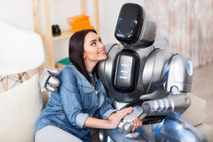 Positive girl and robot bonding to each other. Real friends. Positive delighted girl and robot sitting on the sofa and expressing gladness while bonding to each Royalty Free Stock Photo